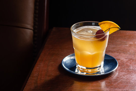 Amaretto Sour Cocktail on the Rocks with a Cherry and Orange Garnish in a Dark Luxurious Bar