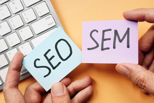 Hands holding cards with SEO and SEM.