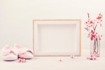 Mock up with empty picture frame, pink tender spring flowers and small baby girl shoes