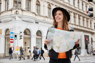 Fototapeta Young positive tourist holds travel paper map, reads route of trip, goes sightseeing, searches destination, gets to right place wears black headgear and leather jacket focused away with pleasant smile obraz