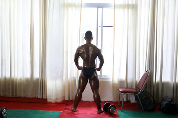 Bodybuilder waits backstage during the 16th Southeast Asia Bodybuilding and Physique Sports Championships in Yangon