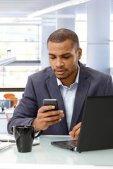Afro american businessman with mobile phone
