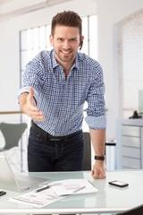 Businessman at office desk offering hand