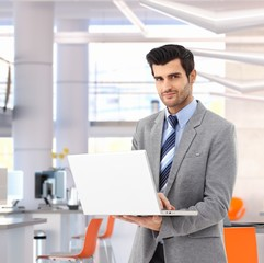Confident businessman with laptop at bright office