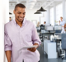 Casual black businessman with tablet at office