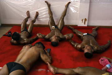 Bodybuilders rest backstage during the 16th Southeast Asia Bodybuilding and Physique Sports Championships in Yangon