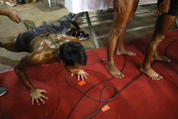 Bodybuilders prepare backstage during the 16th Southeast Asia Bodybuilding and Physique Sports Championships in Yangon