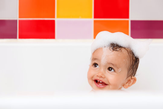 Smiling baby in bathtub with foam bubbles on top of head