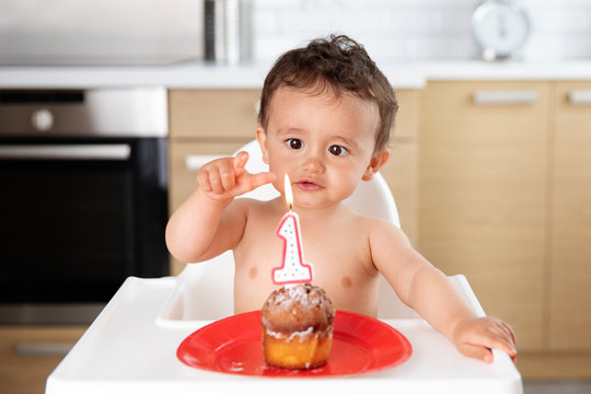 Baby trying to touch candle flame on first birthday