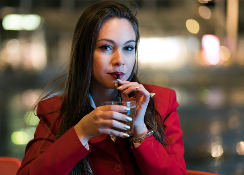 Young woman holding a drink at a night club outdoor