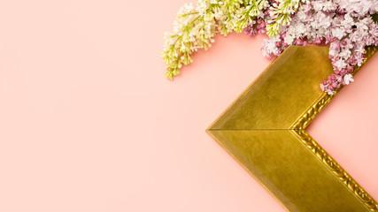 Corner of art frame with lilac flowers on pink background. Framing workshop concept.