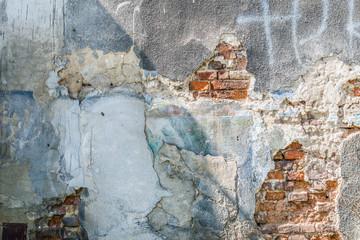 Crumbling, breaking white render on old brick wall