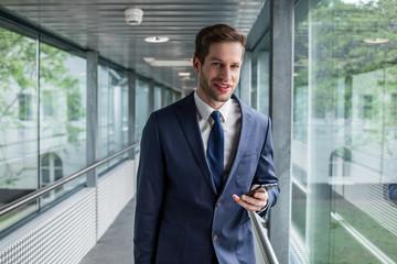 f083cf4b19ff9 Business Man im Anzug lacht und hält ein Handy in der Hand