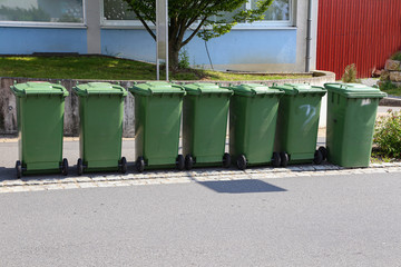 Green garbage cans are on the street