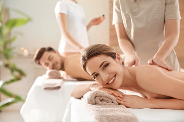 Romantic young couple enjoying back massage in spa salon