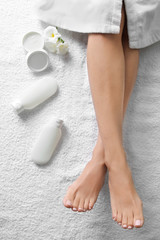 Woman with beautiful feet and cosmetic products on white towel, top view. Spa treatment