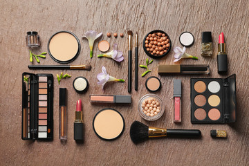 Many different makeup products and spring flowers on color background, flat lay