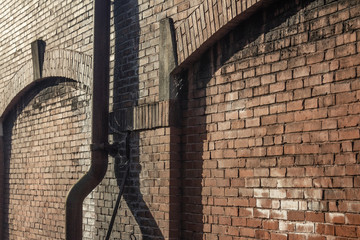 Old brick wall exterior of an old warehouse, pipes, perspective view, horizontal aspect