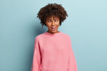 Crazy funny dark skinned woman crosses eyes, makes grimace, sticks out tongue, foolishes indoor, has curly hair and dark skin, isolated over blue background. Human facial expressions, craziness