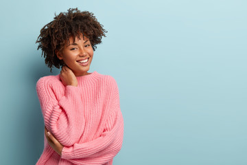 Studio shot of glad charming young female with Afro haircut, touches neck, wears oversized jumper, isolated over blue background with blank space for your promotional content. Pleasant emotions
