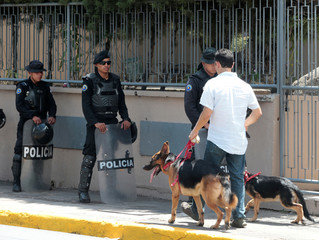 A man walks with dogs past riot police officers standing guard outside the Mologuina church, where coffin with the body of U.S. citizen Eddy Montes, who was killed in a prison shooting is displayed, in Matagalpa