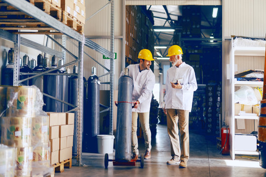 Smiling young Caucasian employee transporting bottle with gas while manager holding tablet and talking to worker. Warehouse interior.