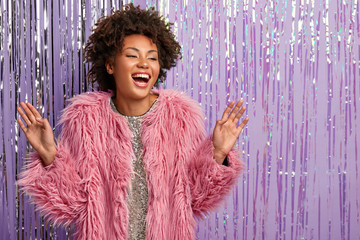 Smiling carefree Afro American woman has makeup, curly hair, dances actively, dressed in pink fur coat, moves actively, has overjoyed facial expression, poses over purple wall with blank space