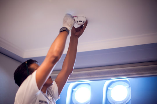 A man worker fix fire system on the ceiling. Building, renovation and electricity concept