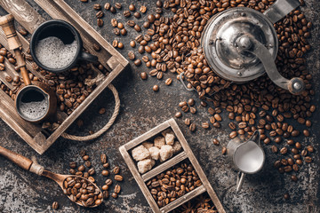 Coffee on wooden tray with coffee beans on dark textured background. Top view with copy space. Background with free text space.