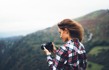 Wall Mural - hipster tourist girl hold in hands modern photo camera, photographer look on camera technology take photography click, journey landscape vacation concept, wind mountain