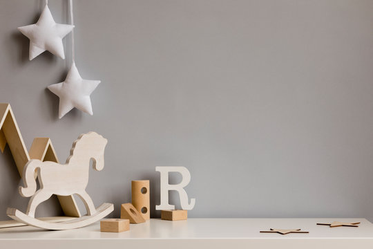 Stylish and cozy childroom with  wooden mountain box, horse, blocks and hanging white stars on the gray wall. Bright and sunny interior. Copy space. Minimalistic childish decor. Template.