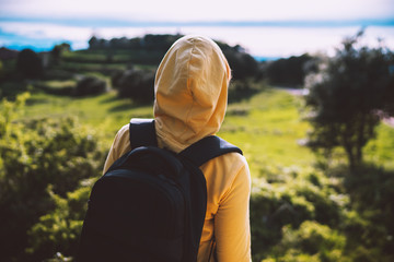 Wall Mural - tourist traveler with yellow backpack standing on green top on mountain, hiker view from back looking on hills, girl enjoying nature panoramic landscape in trip, relax holiday concept