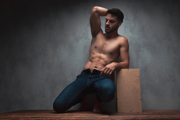 Sensual young guy kneeing and leaning on a box