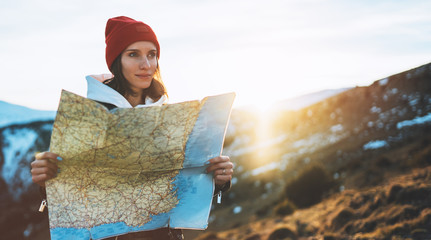 Wall Mural - traveler girl hold in hands map and look landscape vacation trip, people planning trip, hipster tourist on background sun flare nature, enjoy lifestyle holiday concept, sun mountain