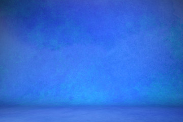 photo background blue. textured wall rolling in the floor. studio photography background illuminated by the directed light fabric painted canvas