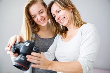 Mother and daughter taking photos and checking them on a modern digital DSLR camera