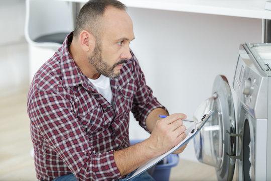 mature serviceman inspecting washing machine
