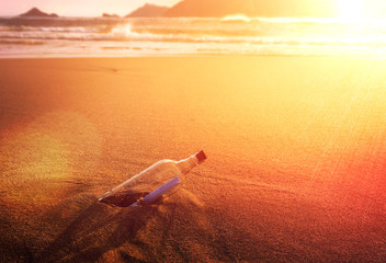 Message In A Bottle Glass Corked On Ocean Beach At Golden Sunset Conceptual