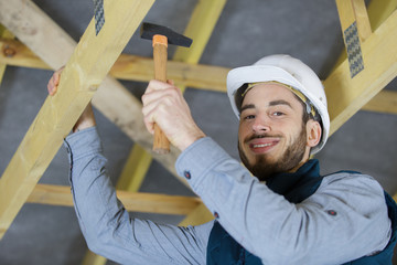 happy roofermaker using a hammer in traditional construction