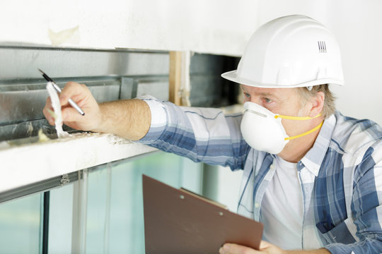 male tradesman wearing a mask inspecting property