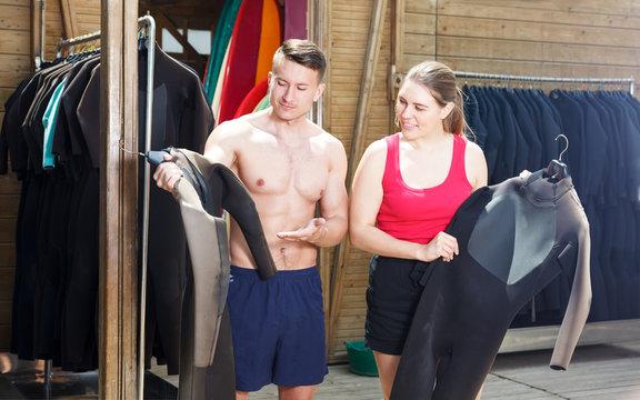 Couple choosing wetsuit in surf club
