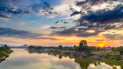 Mekong River Pakse Laos sunset dramatic sky reflection on water village on riverbank travel destination in South East Asia
