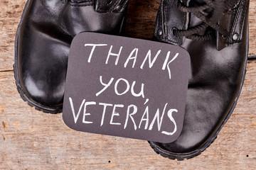 Thank you veterans concept. Close up black shiny boots.