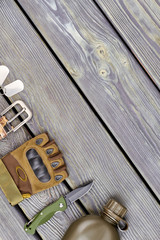 Military glove, knife and bottle on wood. Top view, flat lay. Accessories arrangement with copyspace.