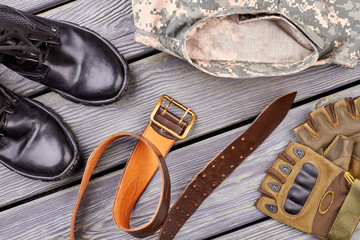 Military outfit equipment. Black shiny boots, belt, gloves and jacket.