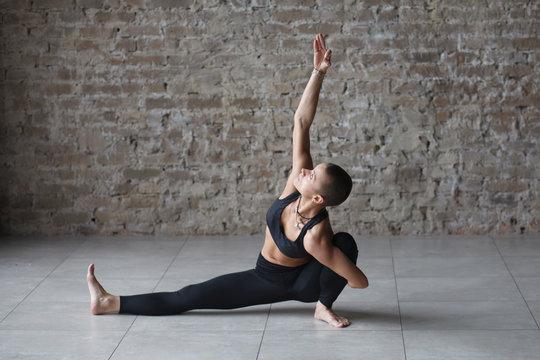 young skinhead woman doing yoga exercise - marichyasana indoor