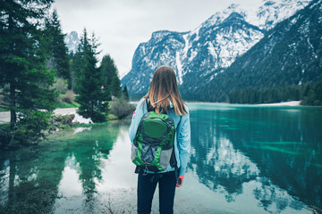 Young woman with green backpack is standing on the coast of mountain lake at cloudy day in spring. Travel in Dolomites, Italy. Landscape with girl, reflection in water, snowy rocks, trees. Vintage Wall mural