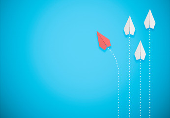 red paper airplane on blue background goes different direction