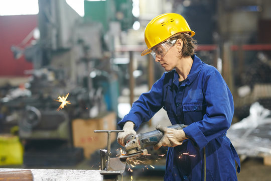 Side view portrait of female worker cutting metal at industrial plant or in garage, copy space