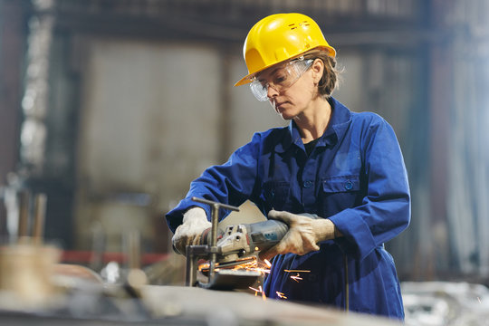 Waist up portrait of female worker cutting metal at industrial plant or in garage, copy space